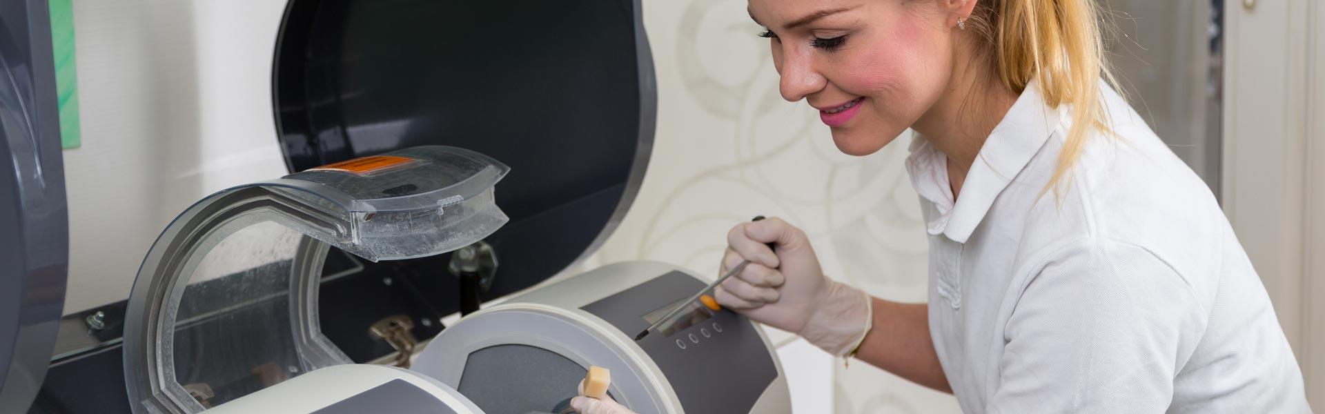 Dental assistant operating CEREC® machine